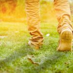 40010489 - a walk towards brighter future, a beautiful shot of feet walking towards sunlight or going ahead towads sunrise or sunset on the grass or park or field running or morning walk or workout, tone added