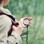 young woman discovering nature in the forest with compass in hand, travel lifestyle concept